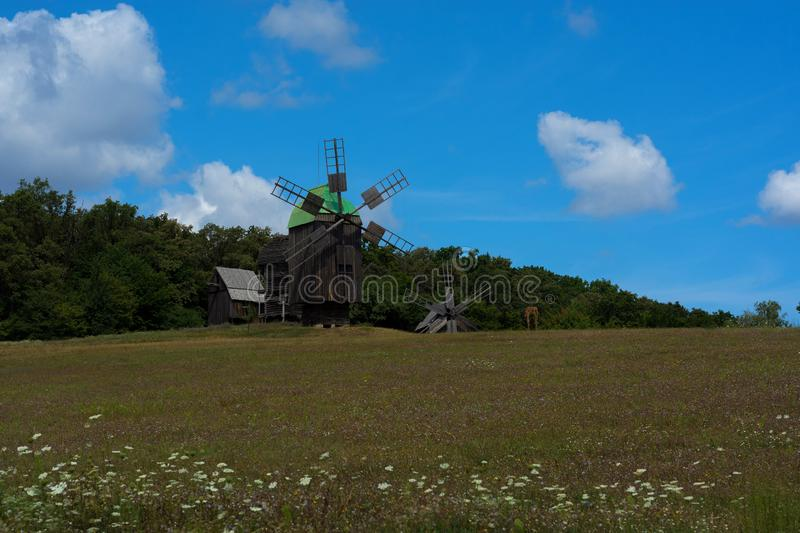 Best photo of windmill on blue sky background and field of flowers. Ukrainian windmill. royalty free stock photos