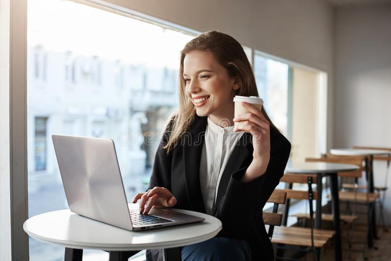 Best place in city with free wifi. Portrait of beautiful stylish urban businesswoman, sitting in cafe, holding cup of royalty free stock images