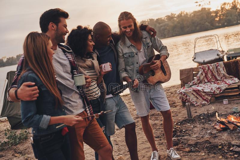 Best place to rest. Group of young people in casual wear smiling while enjoying beach party near the lake royalty free stock photos