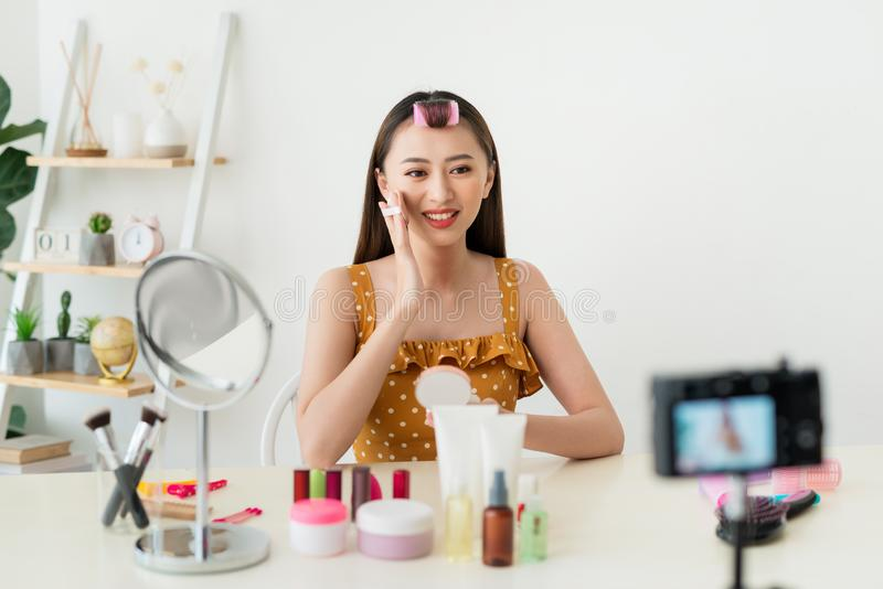 Best powder. Pleasant young woman showing her cosmetics on camera while recommending it to her viewers royalty free stock image