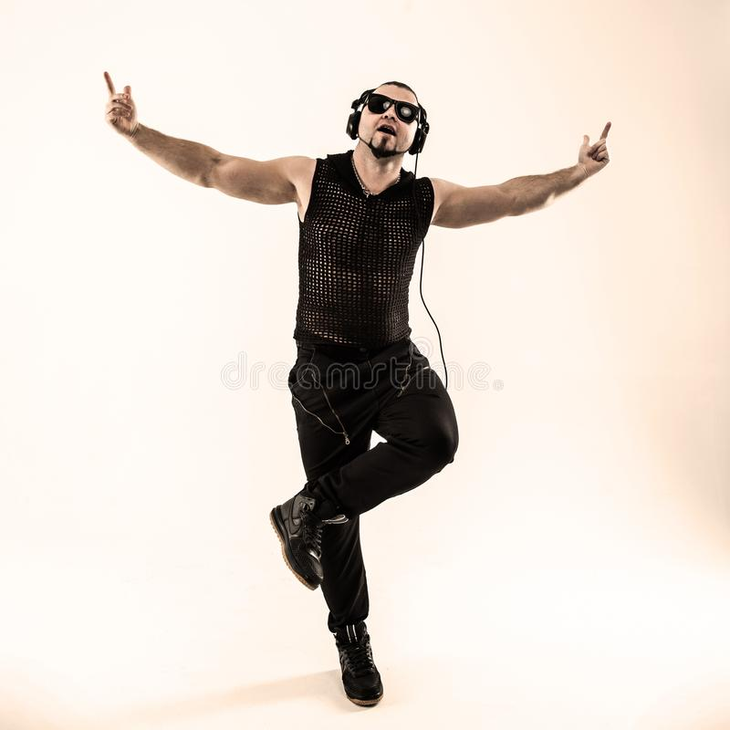 Best rapper dancing break dance .photo on a white background. Rapper with headphones takes breakdancing. photo on a white background and has an empty space for stock images