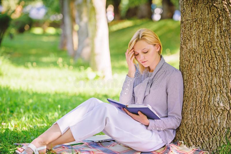 Best self help books for women. Girl concentrated sit park lean tree trunk read book. Reading inspiring books royalty free stock photo