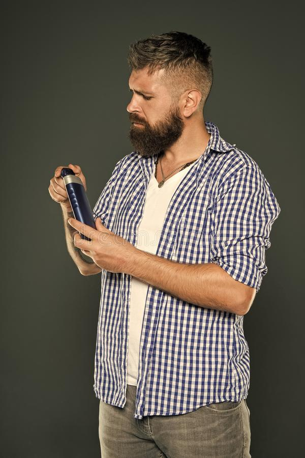 The best shampoo for his hair. Bearded man holding shampoo bottle on grey background. Hipster with beard and mustache royalty free stock photo