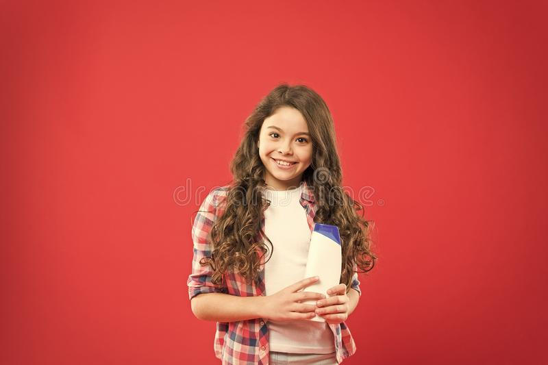The best shampoo for kids hair. Little girl holding shampoo bottle on red background. Small child with long curly royalty free stock images