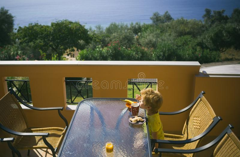Best summer day. Breakfast on the terrace. Apartments near the sea. Greek morning. Food for children. royalty free stock photo