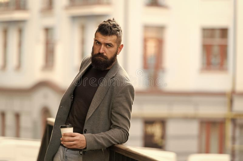 The best time of day to drink coffee. Hipster with reusable paper cup walking in city. Bearded man enjoying morning royalty free stock image