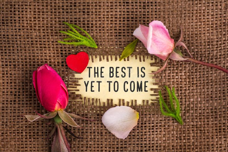 The best is yet to come written in hole on the burlap. With rose flowers and wooden red heart royalty free stock photography