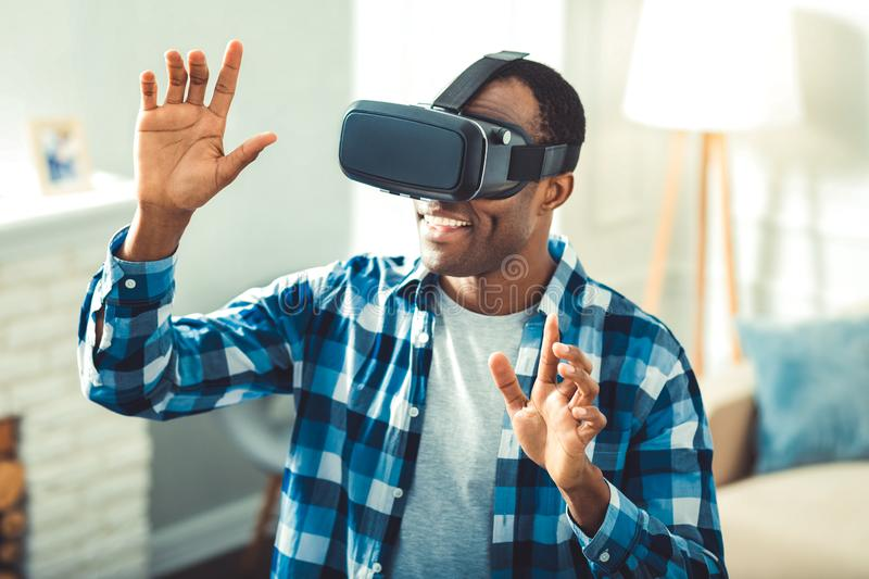 Positive young afro american man building VR. Best VR. Energetic afro american man putting on VR glasses and creating VR image royalty free stock images