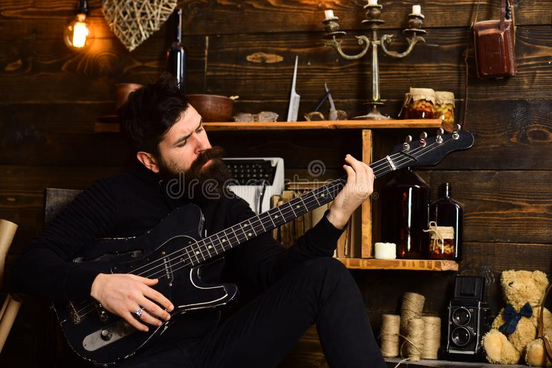 Best weekend. Man with beard holds black electric guitar. Guy in cozy warm atmosphere play relaxing soul music. Man royalty free stock image
