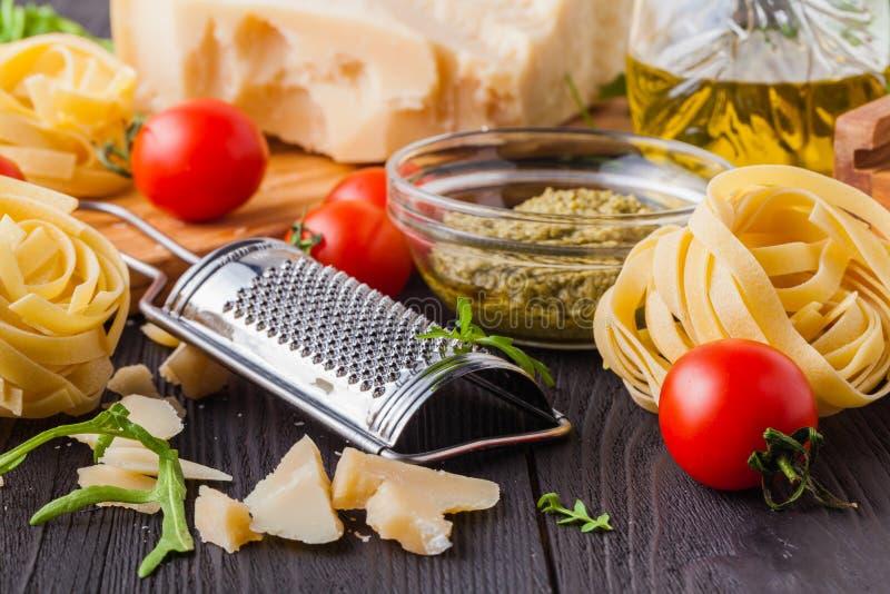 Bestandteile bereit zum Kochen des köstlichen italienischen Abendessens für zwei: Teigwaren, Knoblauch, Kirschtomaten, Rot und gr lizenzfreies stockbild