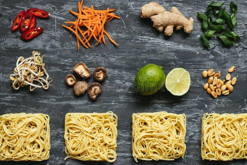 Bestandteile für asiatischen Teller Getrocknete asiatische Nudeln mit Kalk, Nüssen, Koriander und Gemüse auf hölzernem Hintergrun lizenzfreies stockbild