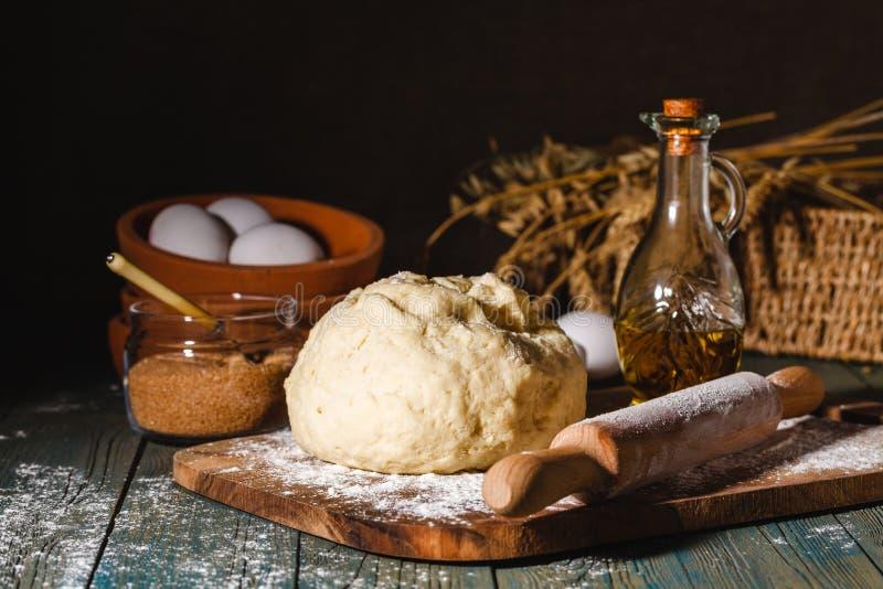 Bestandteile für backende Hörnchen - Mehl, hölzerner Löffel, Nudelholz, Eier, Eigelbe, Butter diente auf hölzernem Hintergrund lizenzfreies stockfoto