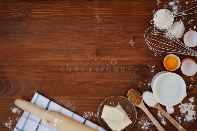 Bestandteile für backenden Teig einschließlich Mehl, Eier, Milch, Butter, Zucker, wischen und Nudelholz auf hölzernem rustikalem  stockbild