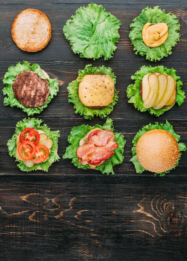 Bestandteile für Burger Neun Burger in den verschiedenen Stadien von Bereitschaft Ansicht von oben Schwarzer hölzerner Hintergrun stockfotografie