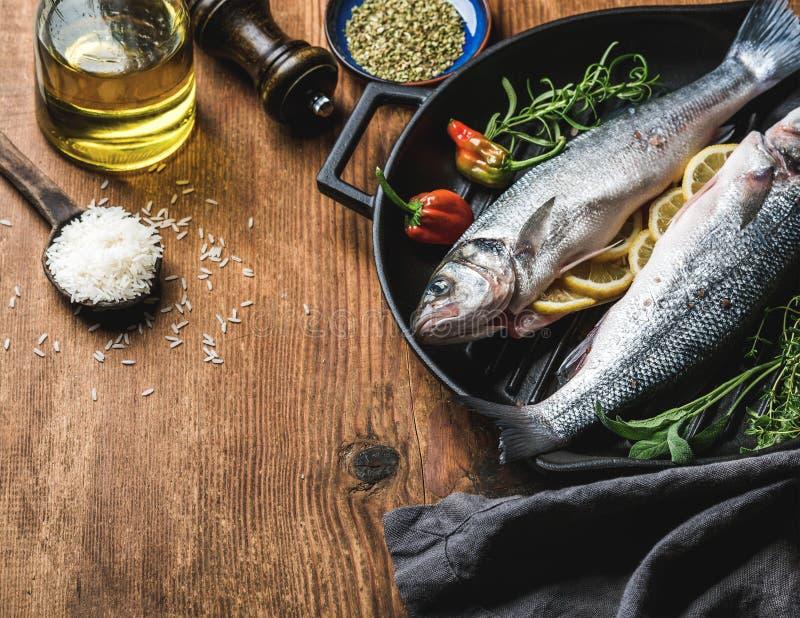 Bestandteile für cookig gesundes Fischabendessen Roher ungekochter Seebarsch mit Reis, Olivenöl, Zitronenscheiben, Kräutern und G stockfotografie