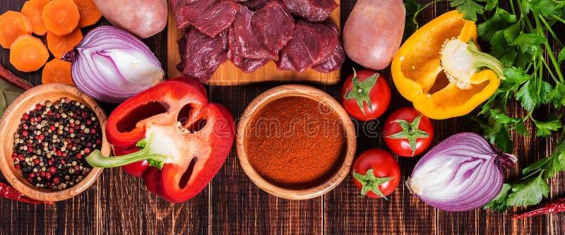Bestandteile für das Gulaschkochen: rohes Fleisch, Kräuter, Gewürze, Gemüse stockfoto