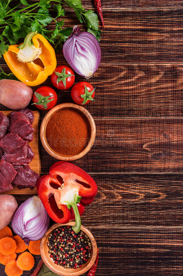 Bestandteile für das Gulaschkochen: rohes Fleisch, Kräuter, Gewürze, Gemüse lizenzfreie stockbilder