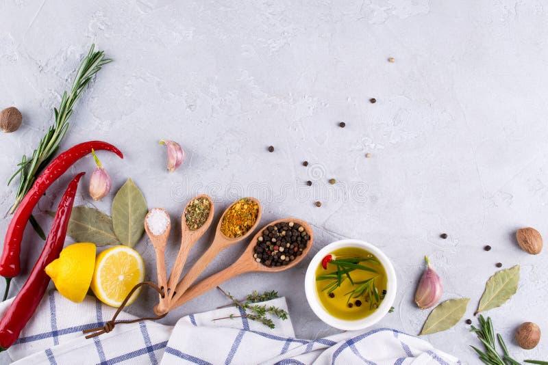 Bestandteile für das Kochen Auswahl von Gewürzen und von Kräuter Lebensmittelhintergrund auf grauer Tabelle stockfotografie