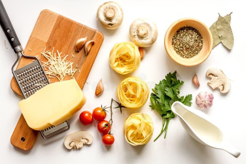 Bestandteile für das Kochen der Paste auf Draufsicht des weißen Hintergrundes lizenzfreie stockfotos