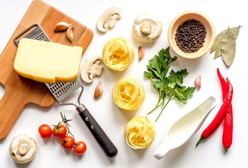 Bestandteile für das Kochen der Paste auf Draufsicht des weißen Hintergrundes lizenzfreies stockbild