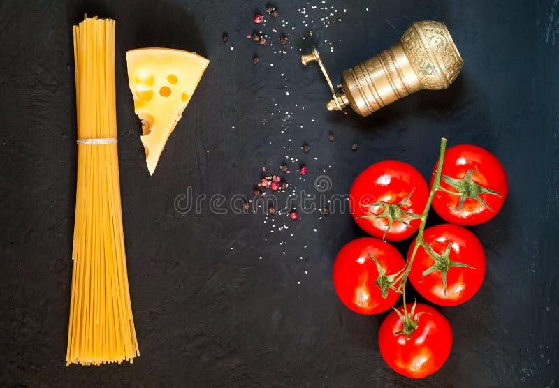 Bestandteile für das Kochen der Paste auf dunklem Hintergrund Feld des biologischen Lebensmittels Das Konzept des vegetarischen L stockbilder