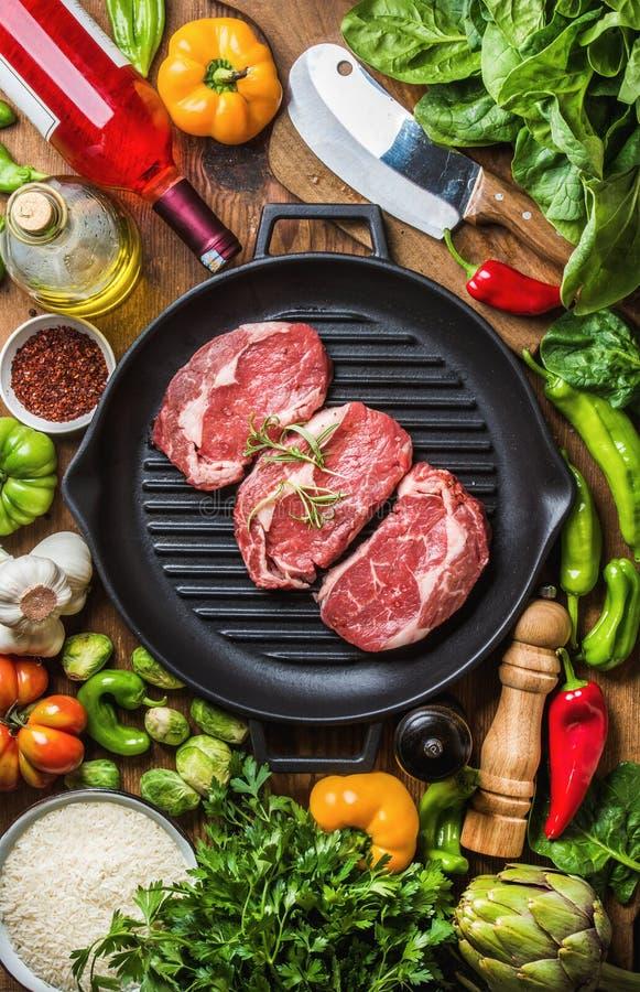 Bestandteile für das Kochen des gesunden Fleischabendessens Rohe ungekochte Rindfleischsteaks mit Gemüse, Reis, Kräutern, Gewürze stockfoto