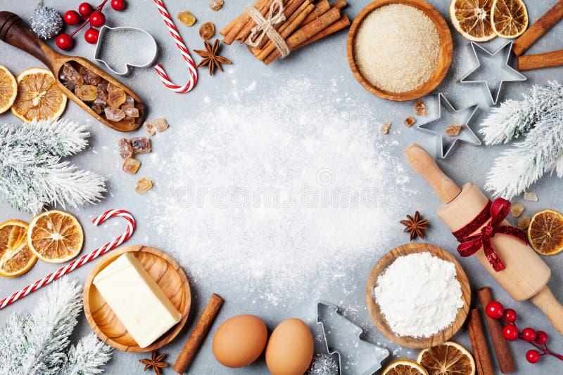 Bestandteile für das Kochen des Weihnachtsbackens verziert mit Tannenbaum Bemehlen Sie, brauner Zucker-, der Eier und der Gewürze lizenzfreie stockbilder
