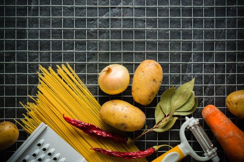 Bestandteile für das Kochen: Kartoffeln, Salz, Pfeffer, Zwiebel, Knoblauch auf einer dunklen Steintabelle Metal Gitter stockfotografie