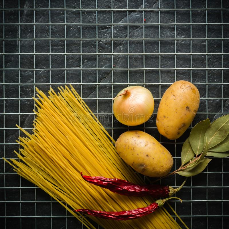 Bestandteile für das Kochen: Kartoffeln, Salz, Pfeffer, Zwiebel, Knoblauch auf einer dunklen Steintabelle Metal Gitter stockfotos