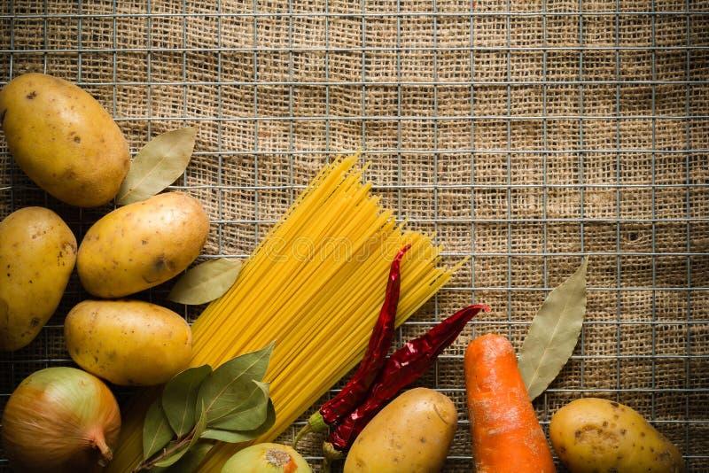 Bestandteile für das Kochen: Kartoffeln, Salz, Pfeffer, Zwiebel, Knoblauch auf einer dunklen Steintabelle Metal Gitter lizenzfreie stockfotos