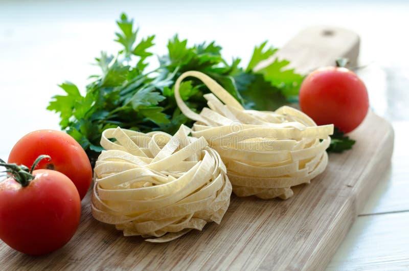 Bestandteile für das Kochen von italienischen Teigwaren - Spaghettis, Tomaten, Basilikum und Knoblauch stockfoto