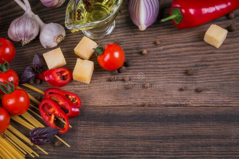 Bestandteile für das Kochen von Spaghettis - rohe Teigwaren, Tomate, Olivenöl, Gewürze, Kräuter stockbilder