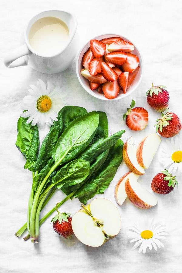 Bestandteile für die Herstellung Kokosnuss des probiotic Joghurts, Spinat, Apfel, Erdbeeredetox Smoothie auf einem hellen Hinterg stockfoto