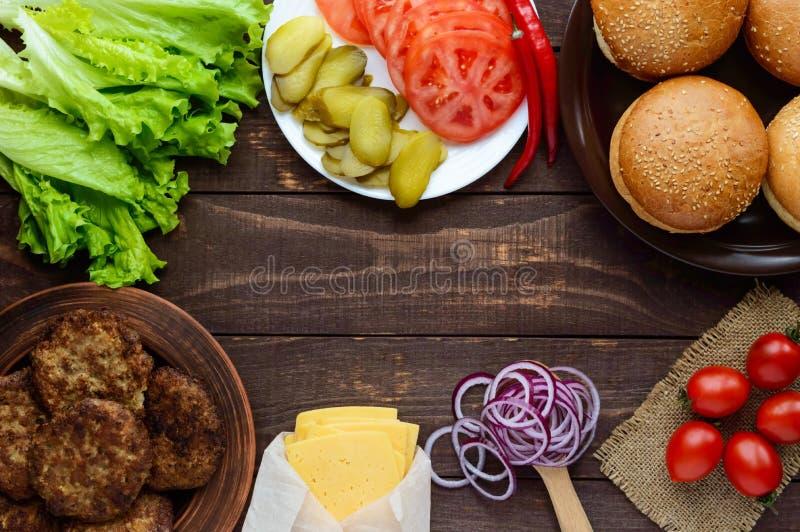 Bestandteile für die Herstellung von Hamburgern (Brötchen, Tomaten, Gurken, Zwiebelringe, Kopfsalat, Schweinekoteletts, Käse) stockfotografie