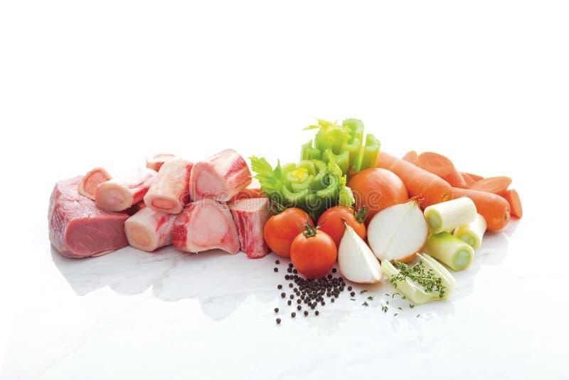 Bestandteile für die Schweinefleischsuppe lokalisiert wie porks, Tomaten, Pfeffer, Zwiebeln, Karotten auf weißem Marmorboden und  lizenzfreie stockfotos