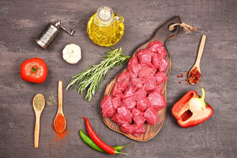 Bestandteile für Gulasch Rohes Rindfleischfleisch und -gewürze breiteten auf dem Tisch aus lizenzfreie stockbilder