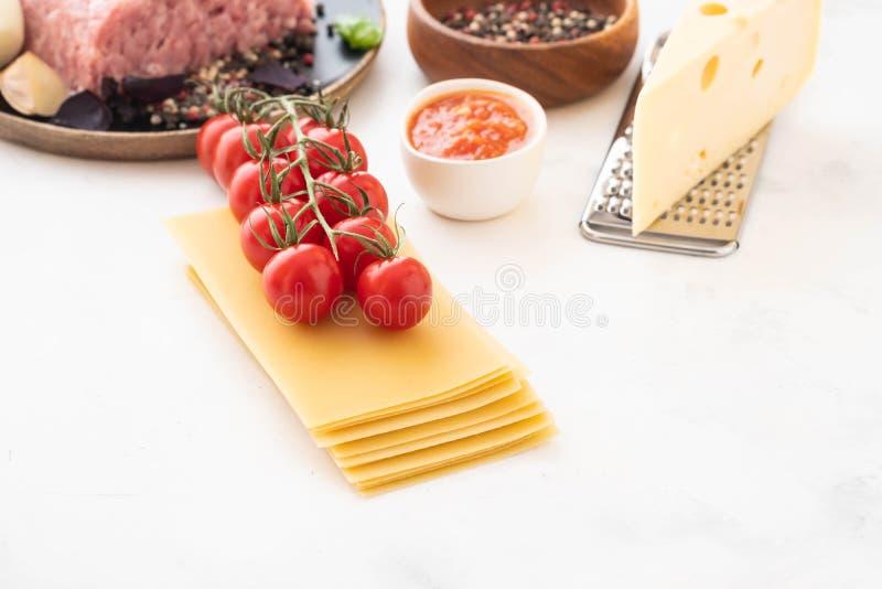 Bestandteile für italienische Lasagne mit frischen Kirschtomaten und grünen Basilikumblättern auf Blättern von getrockneten Teigw stockbild