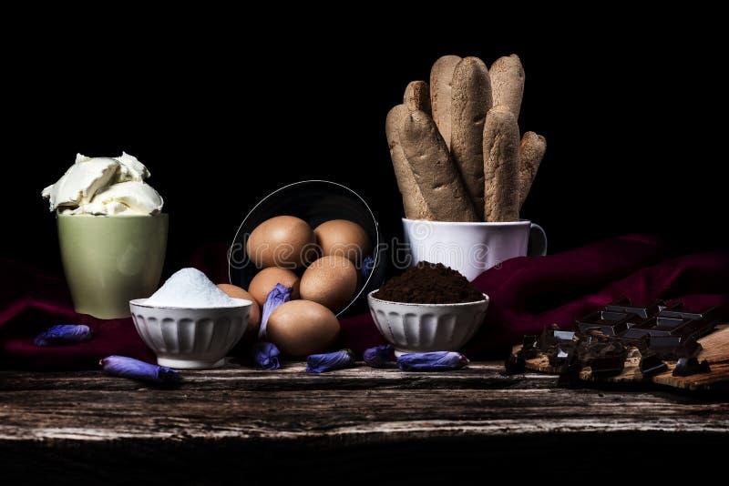 Bestandteile für italienischen Tiramisu, Schokolade, Kaffee und mascarpone auf einem schwarzen Hintergrund lizenzfreie stockbilder