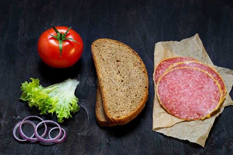 Bestandteile für Sandwich: Brot, Tomate, Salami, Salat, Zwiebel stockbilder