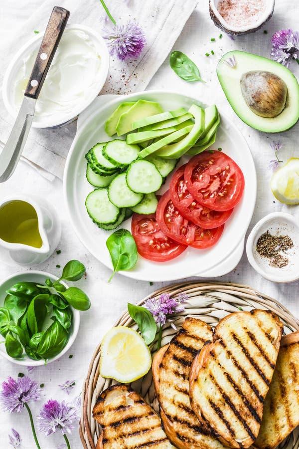Bestandteile für Sandwiche - Frischkäse, gegrilltes Brot, Avocado, Tomaten, Gurken, Schnittlauche auf einem hellen Hintergrund, D lizenzfreie stockbilder