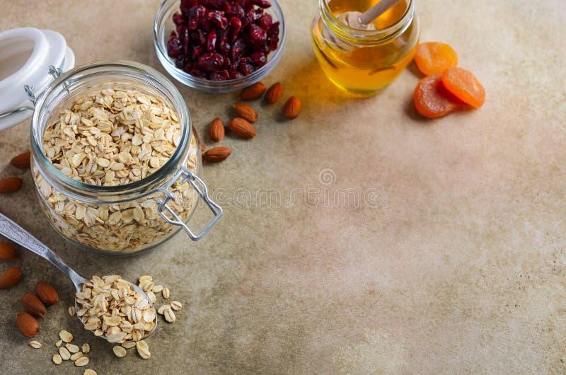 Bestandteile für selbst gemachtes Hafermehlgranola Haferflocken, Honig, Mandelnüsse, trockneten Moosbeeren und Aprikosen Gesundes stockfotografie