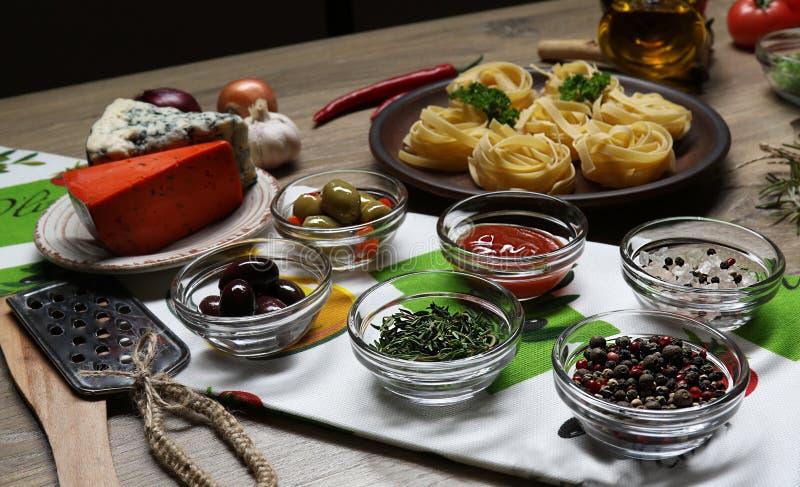 Bestandteile, Gewürze für das Kochen von Teigwaren auf dem Hintergrund von Käsen, Platten mit Teigwaren lizenzfreies stockfoto