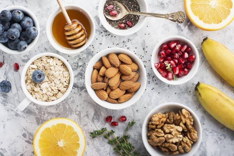 Bestandteile zum ein gesundes Frühstück, Nüsse, Hafermehl, Honig, Beeren, Früchte, Blaubeere, Orange, Granatapfelsamen stockbild