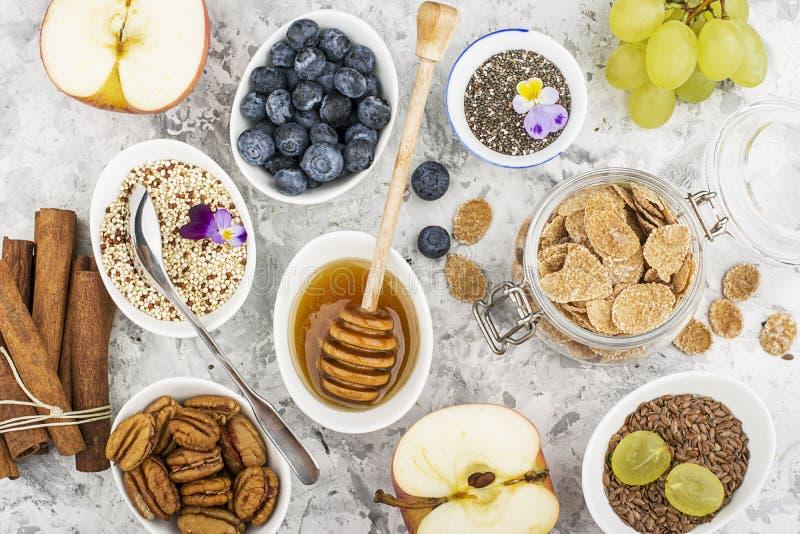 Bestandteile zum ein gesundes Saisonherbstfrühstück: Äpfel, Trauben, Pekannuss, chia Samen, Quinoa, Leinsamen, Honig lizenzfreies stockbild