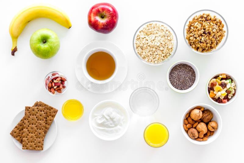 Bestandteile zum gesundes Frühstück trägt, Hafermehl, Jogurt, Nüsse, knusprige Brote, chia auf Draufsicht des weißen Hintergrunde stockbilder
