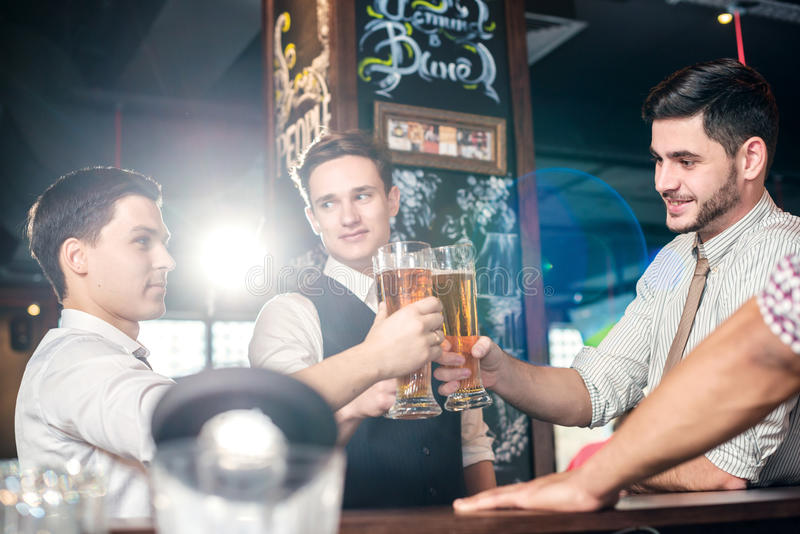 Beste bar voor een bier Vier vriendenmensen die bier drinken en F hebben stock afbeeldingen
