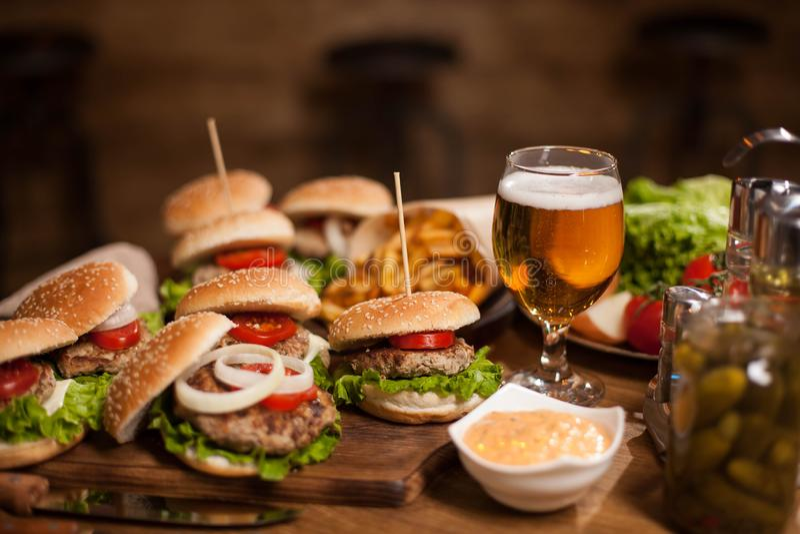 Beste Burger der glücklichen Stunde mit kaltem Bier auf einem Restaurantholztisch lizenzfreie stockfotografie