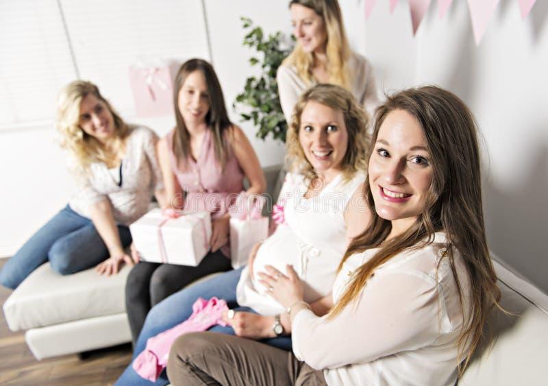 Beste Freunde auf der Babypartypartei, die Kinderkram als Geschenk gebend feiert lizenzfreie stockbilder