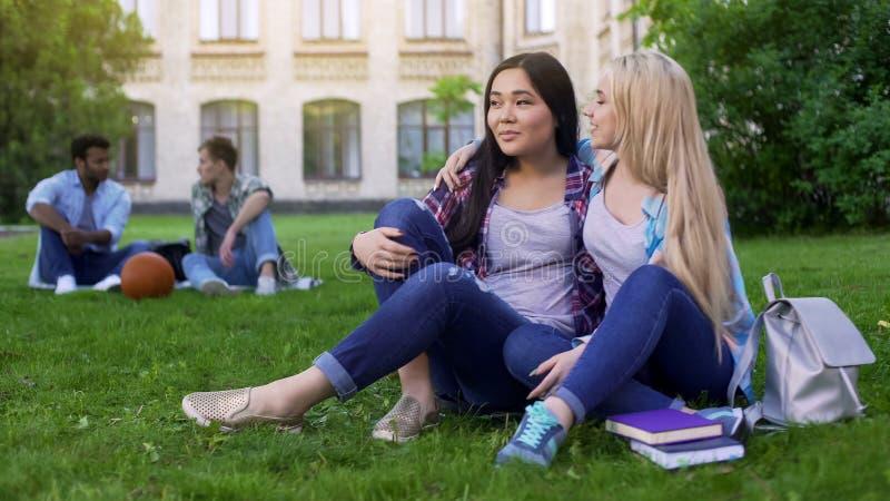 Beste Freunde, die auf Rasen nahe College, dem Umarmen, Unterstützung und Freundschaft sitzen lizenzfreies stockfoto
