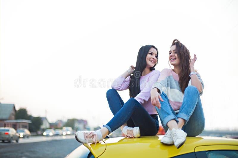 Beste Freundinnen, die mit dem Auto Autoreise bei Sonnenuntergang zujubeln Im Urlaub Ausflug der gl?cklichen Menschen im Freien lizenzfreie stockfotografie